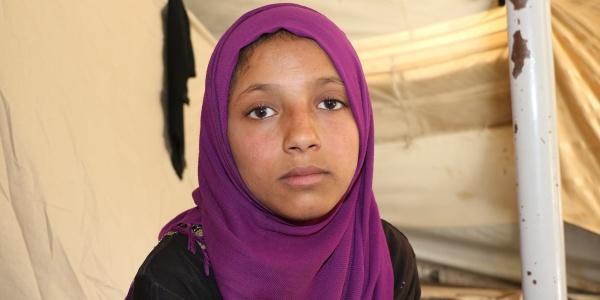 Primo piano di una bambina siriana con chador di colore viola