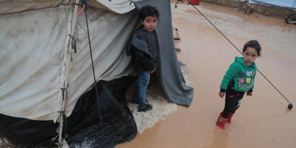 Due bambini siriani fuori alla loro tenda in un campo profughi stanno in piedi nel terreno allagato