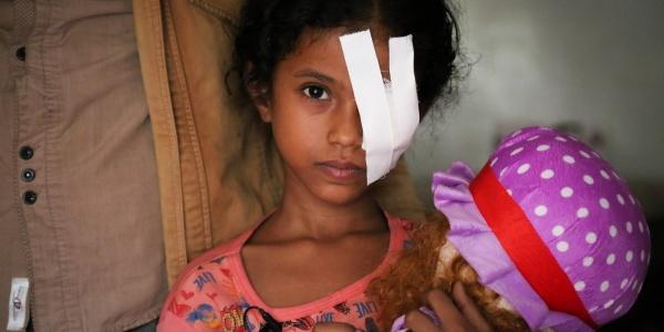Bambina yemenita con bende sull'occhio sinistro abbraccia la sua bambola