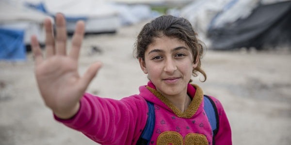 Una bambina siriana fa un gesto a indicare stop con la mano