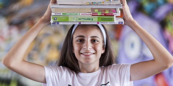 bambina italiana in primo piano che tiene sulla testa dei libri
