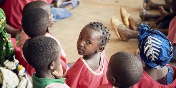 Bambini maliani in cerchio di spalle e al centro una bambina girata guarda in camera
