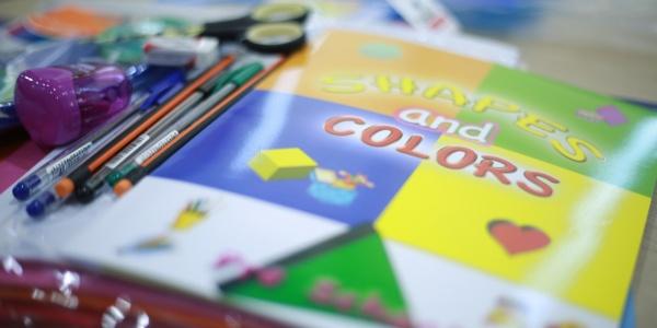 dettaglio di un banco di scuola con un libro colorato con a fianco matite, penne e altri strumenti per il disegno