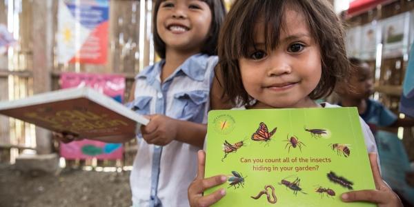 due bambine dentro un aula di scuola tengono in mano un libro a testa. Una di loro guarda in camera sorridente e laltra, sullo sfondo, ride.