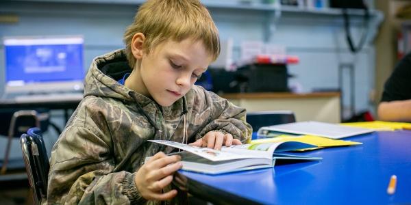 bambino seduto a un tavolo che legge
