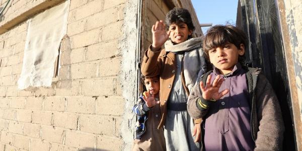 Tre bambini yemeniti in piedi tra due edifici mostrano la mano aperta a cinque