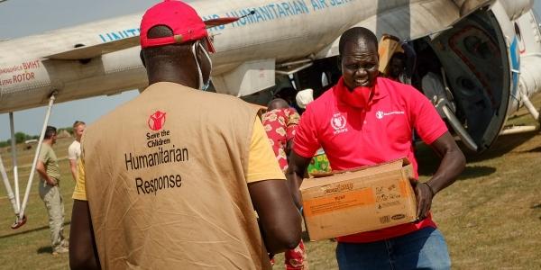 Operatori save the children trasportano in mano scatole di aiuti umanitari appena arrivati da un aereo. Un operatore è di spalle e l altro è di fronte.