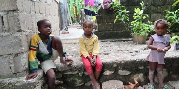 due bambine e una bimba seduti su dei gradini all aperto