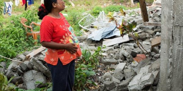 Donna indonesiana in cinta sta in piedi di profilo e guarda di fronte a lei un abitazione distrutta dal terremoto