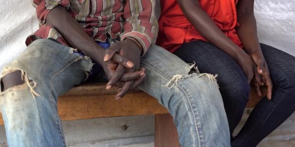 primo piano delle mani di un ragazzo sud sudanese seduto accanto a operatrice