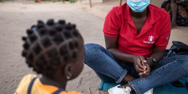 un operatrice save the children in Mozambico è seduta a terra a gambe incrociate e guarda una bambina di spalle seduta di fronte a lei.