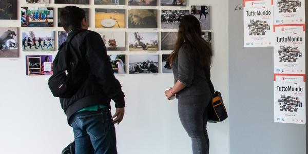 due ragazzi in un museo, in piedi, di spalle, guardano delle fotografie appese a un muro