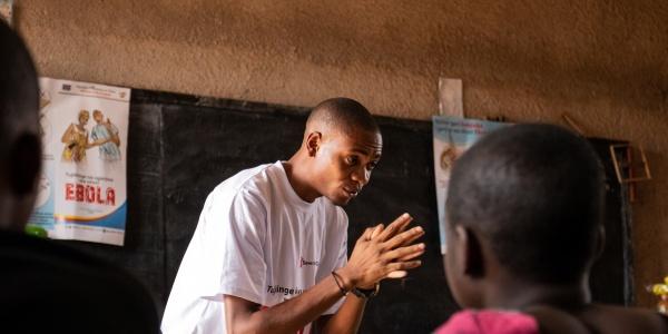 Un operatore spiega le norme igieniche per prevenire il virus ebola, una bambina di spalle ascolta