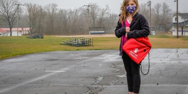 bambina in piedi in un parcheggio con mascherina per proteggersi dal Covid-19 tiene in spalla uno zaino scolastico rosso di Save the Children