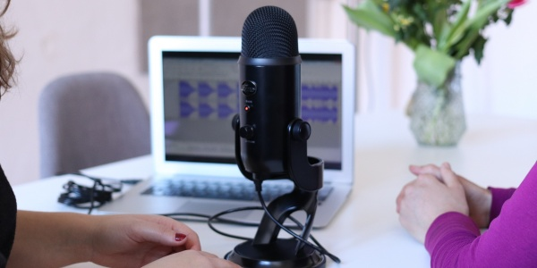 Un microfono con dietro un computer appoggiati entrambi su un tavolo. Si vedono lateralmente mani e braccia d due ragazze sedute allo stesso tavolino