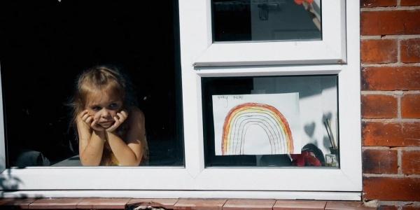 una bambina affacciata alla finestra guarda in basso pensosa. Sulla destra è appeso alla finestra il disegno di un arcobaleno