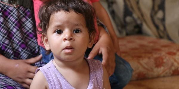 Bambino di 13 mesi con una canottiera rosa è tenuto per le spalle da una donna che non si vede in faccia.