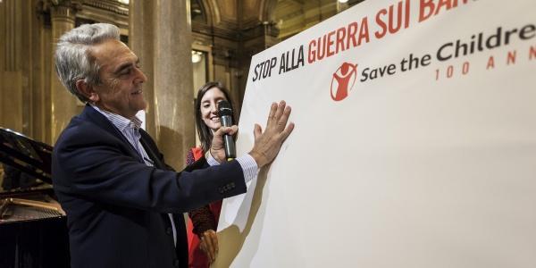 Valerio Neri stampa la sua mano su un cartellone per stop alla guerra sui bambini