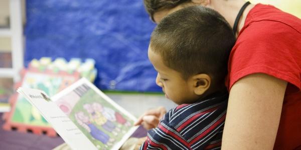 operatrice di save the children aiuta un bambino a studiare
