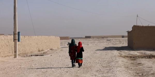 due bambine afghane riprese mentre camminano di spalle in territorio desertico