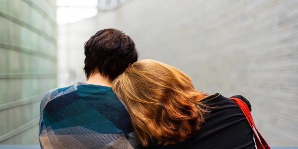 Due donne di spalle, una con capelli biondi lunghi e l altra con capelli corti mori guardano alla finestra. La donna bionda ha la testa appoggiata alla spalla della signora acconto a lei.