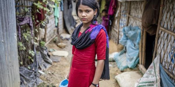 Bambina adolescente in piedi davanti alla sua casa fissa con vestito lungo rosso e scialle viola.