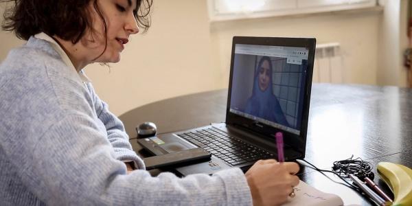 Una ragazza seduta alla scrivania di profilo scrive su un quaderno e davanti a un pc nel cui schermo c è una video chiamata