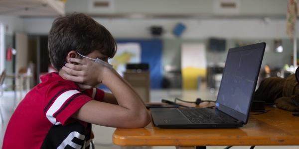 bambino seduto davanti al PC indossa una mascherina per proteggersi dal covid-19