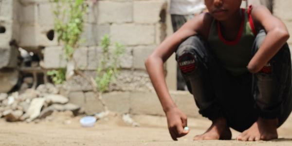 Un bambino è accovacciato a terra, ha un braccio disteso e uno appoggiato alla gamba e non ha una mano.