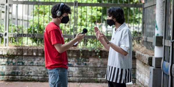Un adolescente con maglia save the children indossa cuffie e tiene in mano un microfono e un registratore ed è proteso verso un altro adolescente con camicia bianca e pantaloni neri