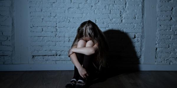 bambina davanti a un muro seduta accovacciata con la testa fra le braccia