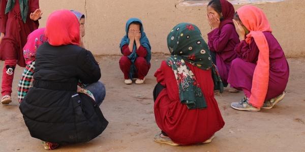 bambine vestite in viole e rosso sono sedute in cerchio e si coprono il volto con le mani.