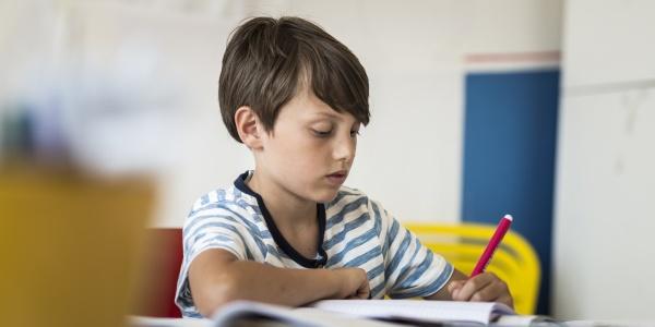 bambino seduto a un banco di scuola mentre disegna