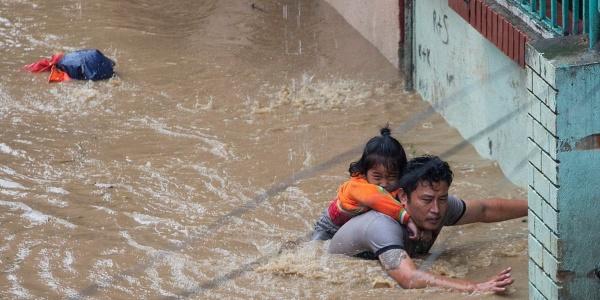 Un padre con la sua bambina che cerca di mettersi in salvo dall acqua alta