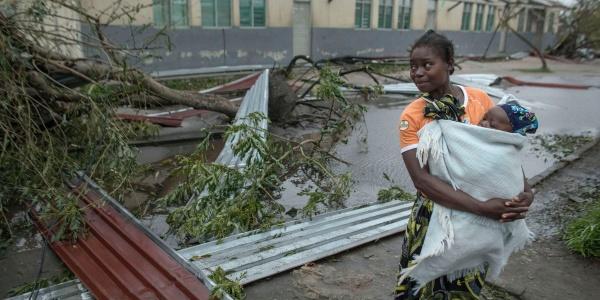 una madre con in braccio il suo piccolo bambino con alle spalle la devastazione provocata dal ciclone Idai che ha distrutto case e allagato intere aree in Mozambico, Malawi e Zimbabwe