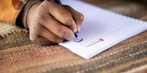 mano di un bambino con penna in mano scrive su una pagina bianca