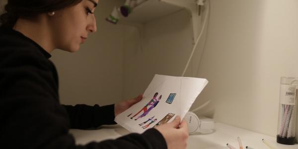ragazza seduta a una scrivania guarda un disegno con immagini violente fatto da un bambino vittima di violenza assistita