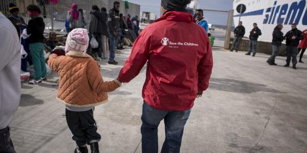 Operatore umanitario save the children mano nella mano con una bambina